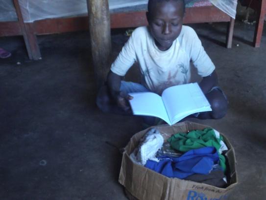 Emmanuel blättert in einem Schulbuch