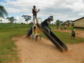 """Janvier und eine Junge rutschen auf dem """"Save the children"""" Spielplatz"""