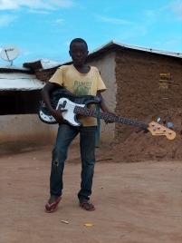 Ein Junge mit der Gitarre von Elvis, dem Leiter des Youth Centres